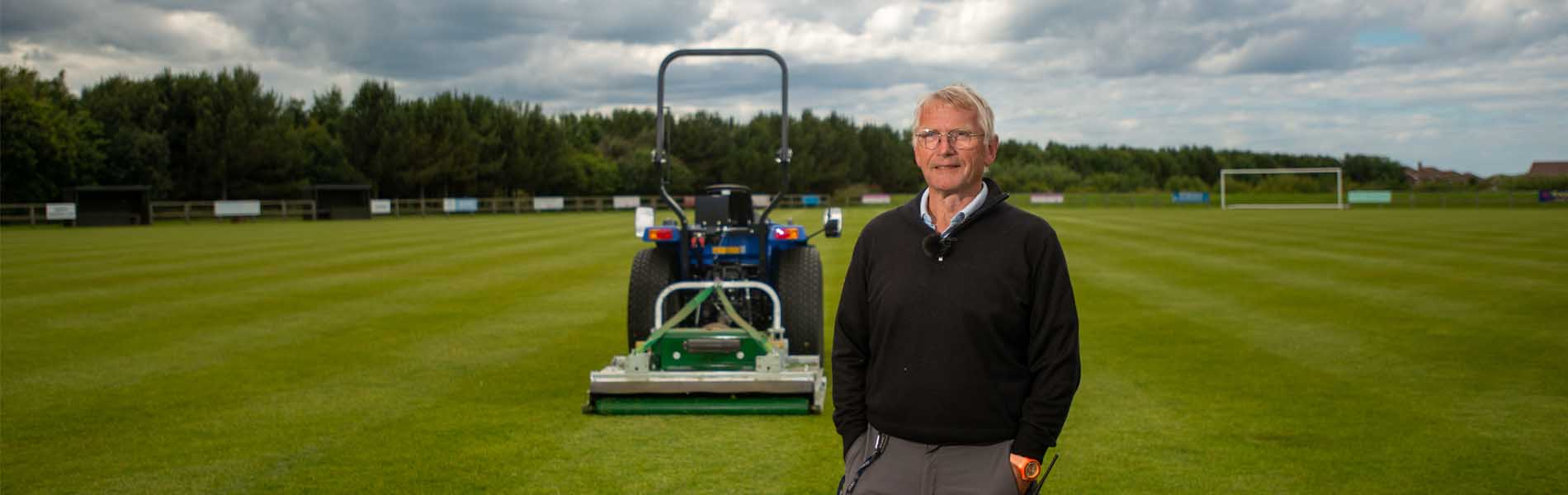 a major mower with a blue compact tractor with the owner